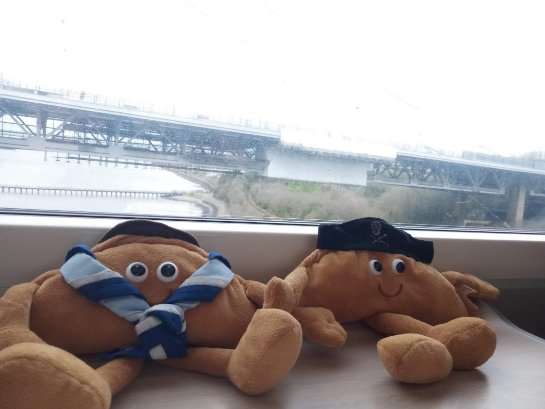 Two plush pasties sit next to each other on a train