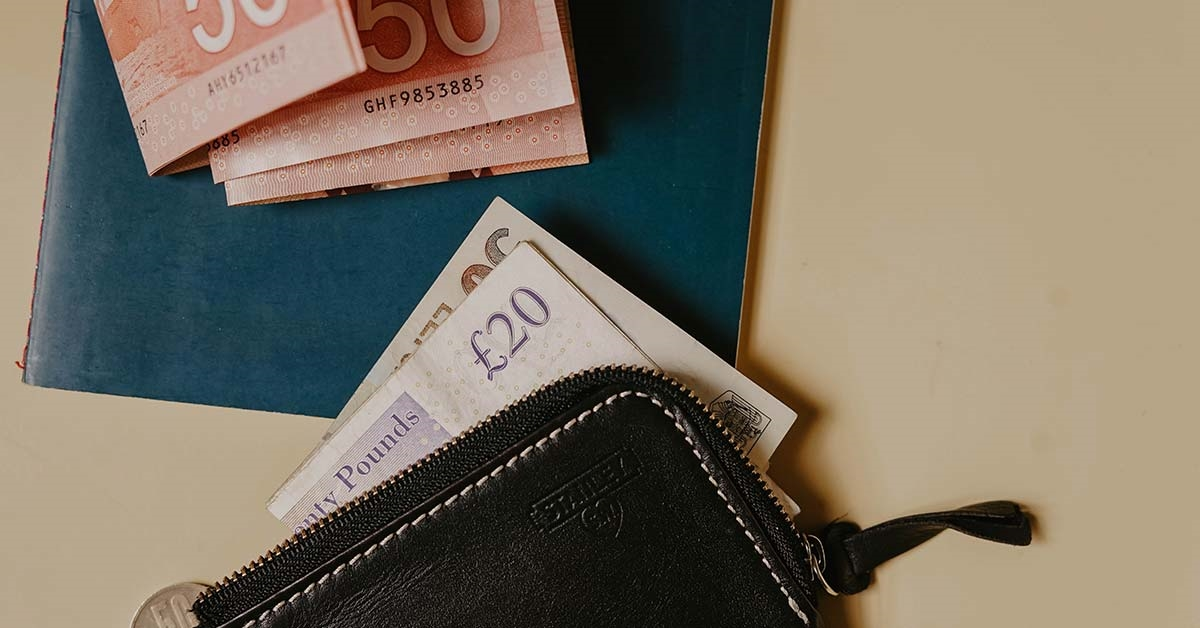 A wallet on a table with a £20 note sticking out