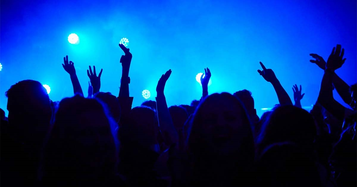 A photo of people with their hands up at a late-night event, with blue lighting and smoke effects