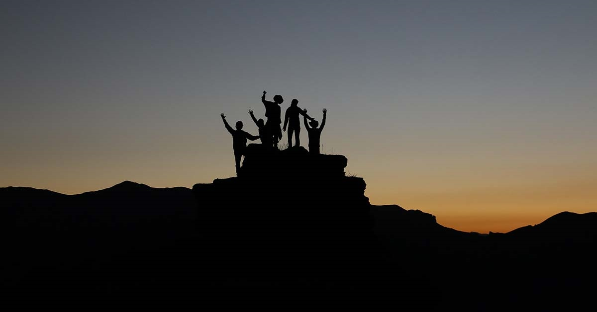 A group of people stood on a hill silhouetted by the sunset