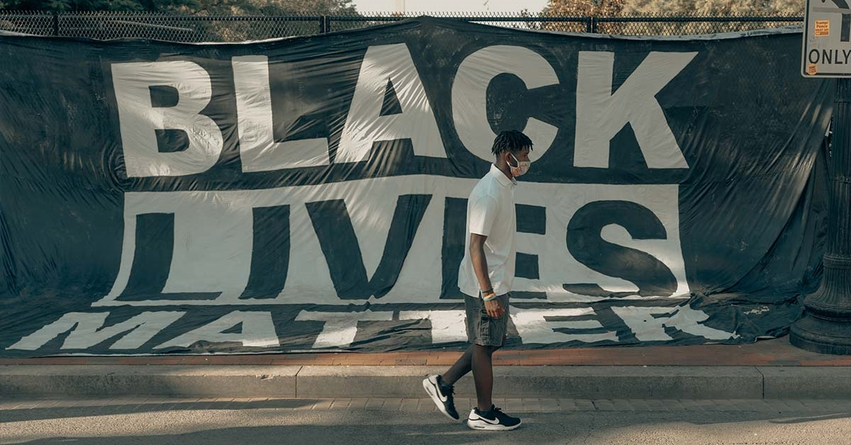 A Black Lives Matter banner hung on a fence with somebody walking past