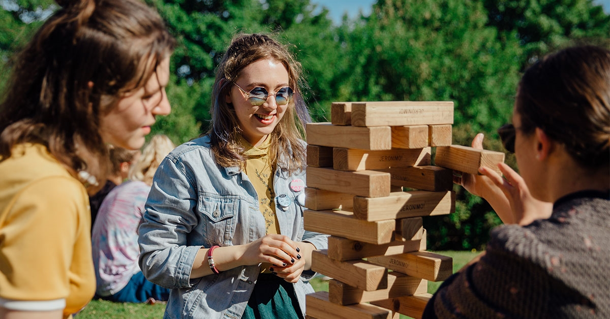 Three students playing giant Jenga in the sun