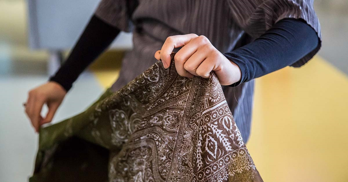 A student holding some fabric
