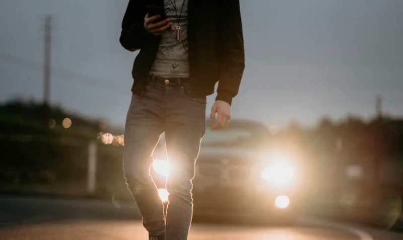 Photo of someone texting whilst walking in a road